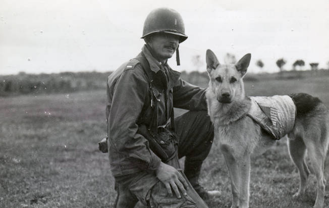 """This German Shepherd, named """"Jaint de Motimorency,"""" poses with his owner, Lt. Peter Baranowski. If you look, paratrooper Baranowski's companion bears the U.S. flag paratrooper insignia; he was the only dog to have actually jumped into combat with American airborne forces."""