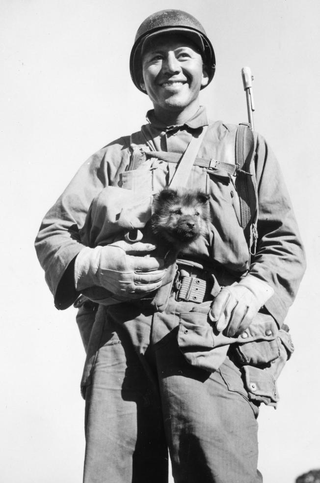 Sgt. Bea Alcoze of Ft. Worth, Texas, carries his canine companion along a hike to a position near Burma Road, as part of the Mars Task Force in Ho-Pong.