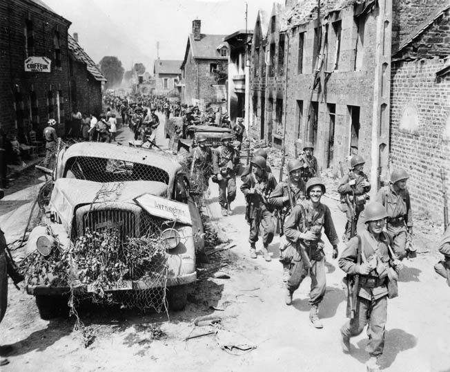 Soldiers of the 8th Infantry advance through the French town of Brehal on their way to Avranches.