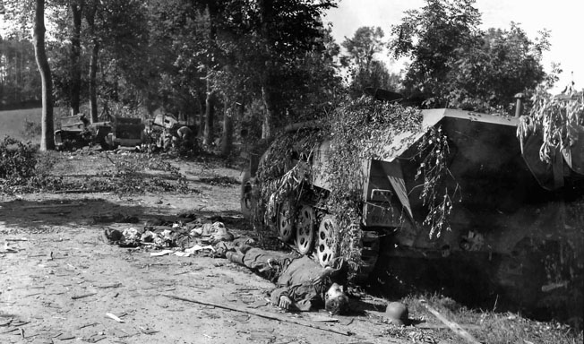 The body of a dead German Waffen SS sergeant lies sprawled beside an armored vehicle that has been knocked out during the fighting around Mortain.