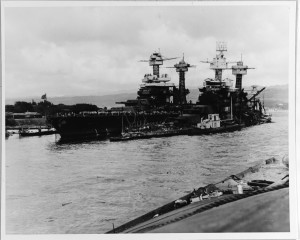 The battleship USS Tennessee is wedged against its mooring quays by the hull of the sunken USS West Virginia, which took several torpedo hits during the attack on Pearl Harbor. Engineers used dynamite to free the hull of the trapped Tennessee, which was repaired and modernized to later return to service.