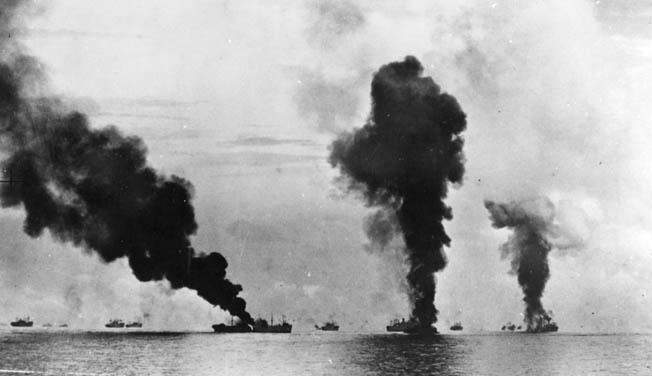 This photo was taken shortly after the one above and depicts the burning transport George F. Elliott, hit by a Japanese plane, at left center. The other columns of smoke are from Japanese aircraft that have been shot down and crashed into the sea.