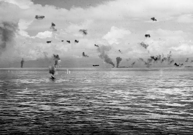 A Japanese Mitsubishi G4M Betty bomber makes a torpedo run against American ships of the Tulagi invasion force. This photo was taken on August 8, 1942. The blazing ship in the distance is probably the transport George F. Elliott.