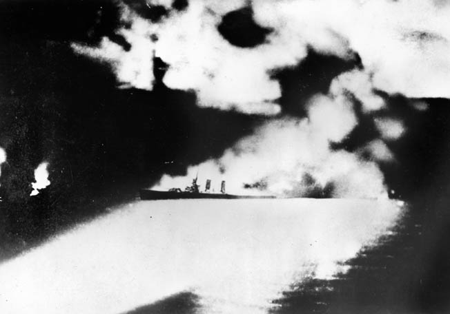The burning cruiser USS Quincy was photographed by a Japanese cameraman at the height of the Battle of Savo Island. In this image, the doomed cruiser is illuminated by flares, searchlights, and the roaring flames that were consuming her before she plunged to the bottom.