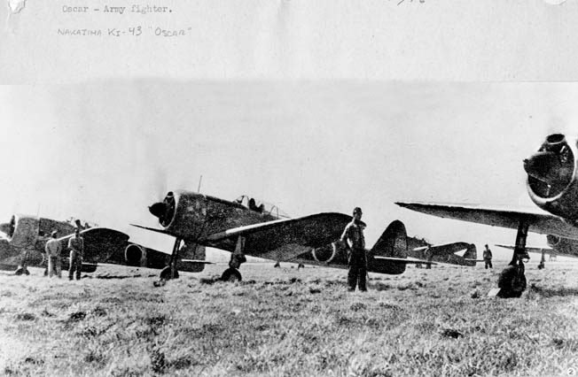 In this captured Japanese photograph, ground crewmen stand near Nakajima Ki-43 Oscar fighters being prepared for a mission. The pilots are in their cockpits and ready for takeoff.