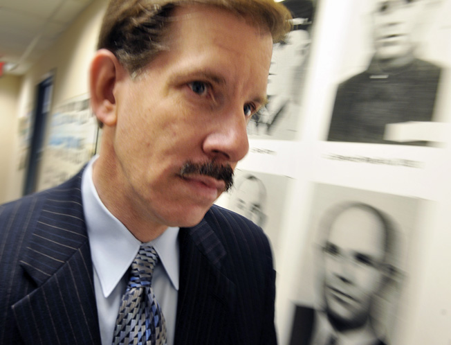 Eli Rosenbaum, director of the Justice Department's Office of Special Investigations, walks down one of the corridors in his office building, this one lined with photos of John Demjanjuk.