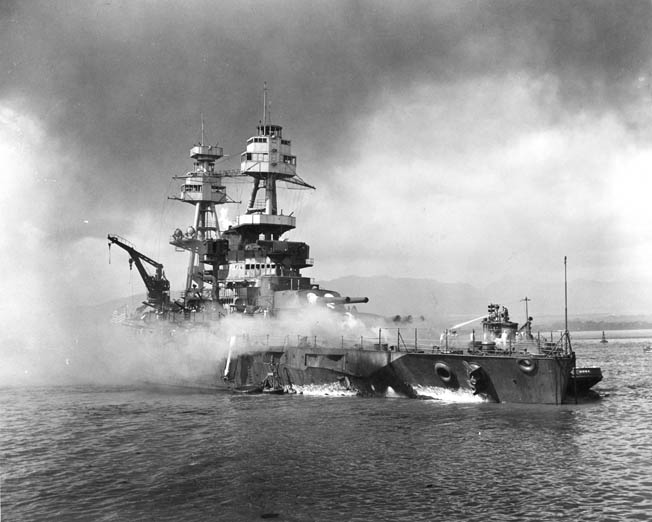 Nevada lies beached and burning at 9:25 am after being hit forward by Japanese bombs and torpedoes. A harbor tugboat is alongside Nevada's port bow, helping to fight fires on the battleship's forecastle.
