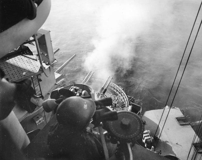 "One of Nevada's 40mm quad ""pom-pom"" gun mounts opens up on Japanese positions at Iwo Jima, February 17, 1945."