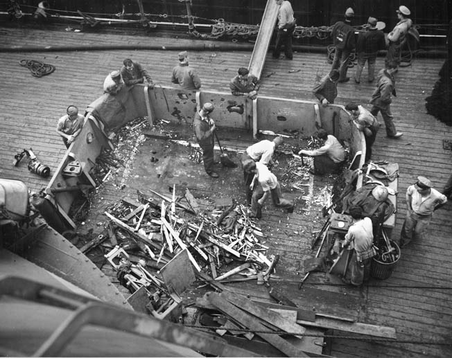 Nevada crewmen clean up damage after Japanese shore batteries on Okinawa zeroed in on her, April 1945.