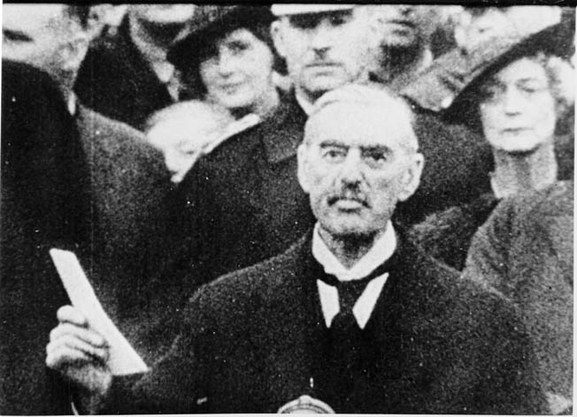 Following his meeting with Hitler at Munich in September 1938, British Prime Minister Neville Chamberlain waves a meaningless treaty that he assures the world preserves '…peace in our time.'