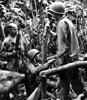 With their tube at maximum elevation, a mortar crew from the 172nd Regiment, 43rd Infantry Division lobs rounds at a nearby Japanese machine-gun nest.