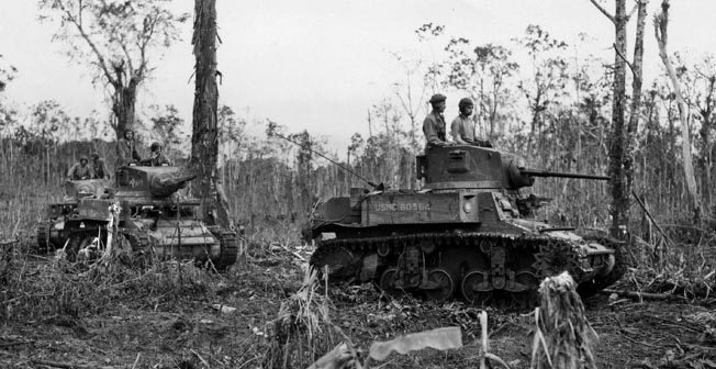 """Three M3 """"Stuart"""" light tanks of the Marine Defense Platoon advance near Munda airfield, August 6, 1943. Fanatical defenders knocked out several tanks before being overrun."""