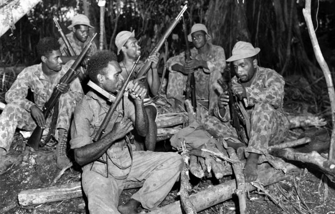 Native soldiers of the 1st Commando, Fiji Guerrillas, under the command of New Zealanders, check weapons before heading out on patrol, July 26, 1943.