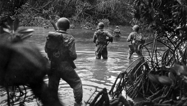 U.S. Army troops warily approach suspected enemy positions on Arundel. The Japanese managed to evacuate a few hundred men from New Georgia before the U.S. declared the area secured.