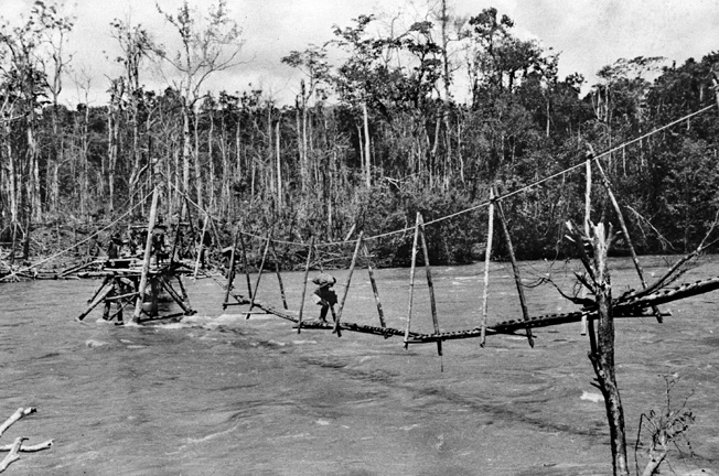 Papuan porters carry supplies on a makeshift bridge over the Kumusi River at Wairopi. This bridge replaced the more substantial bridge destroyed by retreating Australians earlier in the campaign.