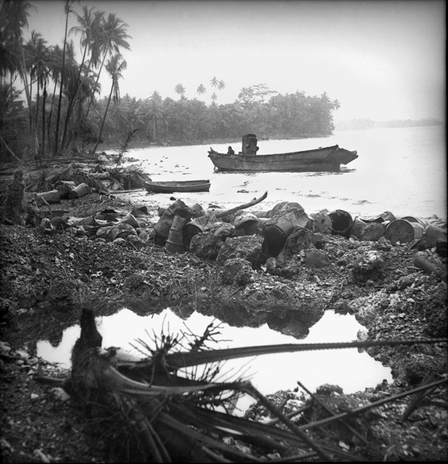 An abandoned Japanese landing barge, riddled with bullet and shrapnel holes, drifts off the Milne Bay invasion beach. Here the Japanese had their string of successful island conquests broken.