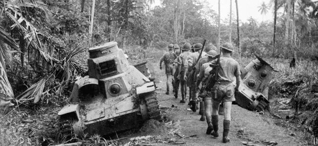 An Australian patrol passes two Japanese Type 95 Ha-Go light tanks knocked out during the fighting for Milne Bay. The last soldier carries an American Thompson .45-caliber submachine gun, supplied by the United States.