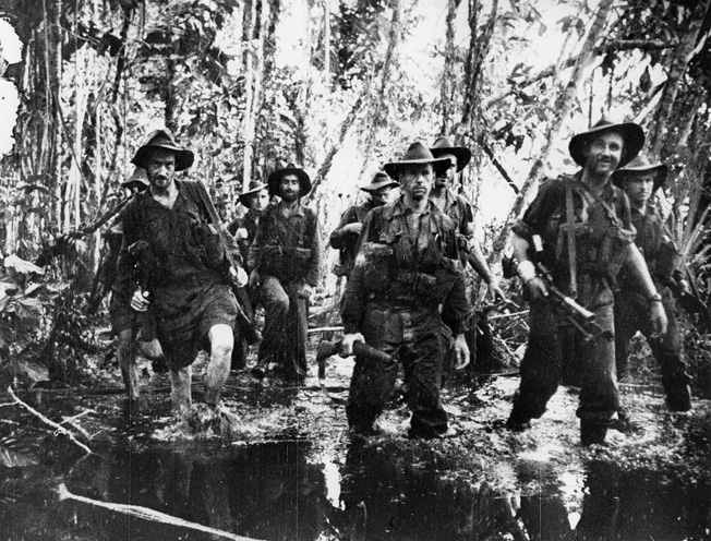 Muddy and rain-soaked members of the Australian 2/7 Cavalry Regiment move toward Buna, still confident in the face of savage enemy resistance. The smiling soldier at right carries a 23-pound, .303 Bren light machine gun.