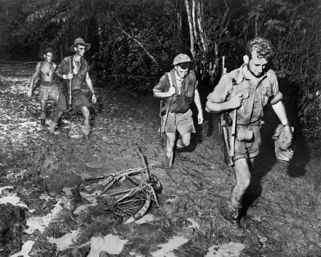 Wading through swamp, Australians keep the pressure on the Japanese retreating back to Buna, November 1942, marking Japan's first reversal on its road to conquest.