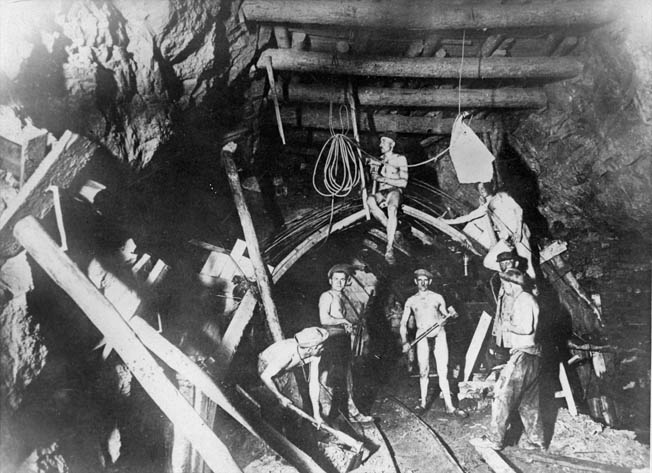 Miners chip away at coal in the warm temperatures of a mine. Nobles spent nine months working in a coal mine as a POW.