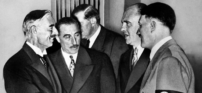 Shaking hands following the betrayal of Czechoslovakia at Munich on September 30, 1938, British Prime Minister Neville Chamberlain (left) and German Chancellor Adolf Hitler (far right) part company after the conference that sealed the fate of the Czech nation. Chamberlain erroneously proclaimed that the deal struck at Munich had preserved peace in Europe.