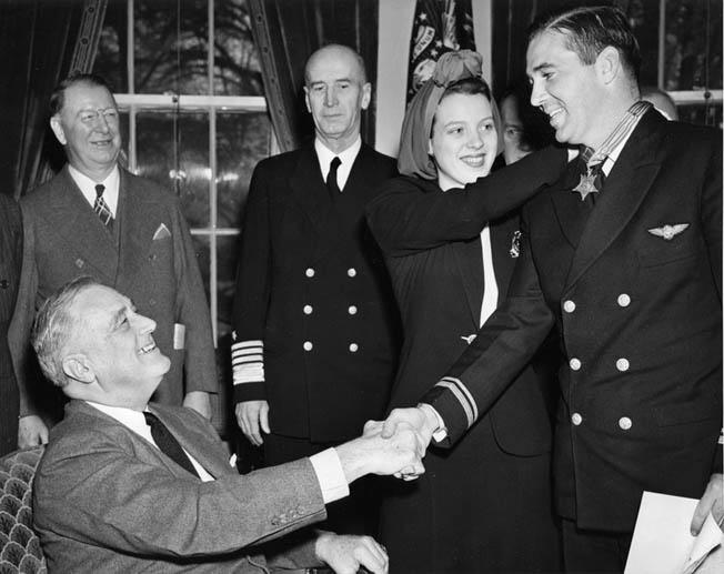 O'Hare shakes hands with President Roosevelt as his wife Rita fastens the Medal of Honor around his neck, April 21, 1942. He was promoted to the rank of lieutenant at the same time.