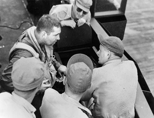 "Lt. Cmdr. O'Hare (left) talks with leading crew chief ""Chief Willy"" Williams and others beside an F6F-3 Hellcat aboard the Enterprise after action over Wake Island, October 5, 1943. O'Hare vanished during combat over the Gilbert Islands on November 26, 1943."