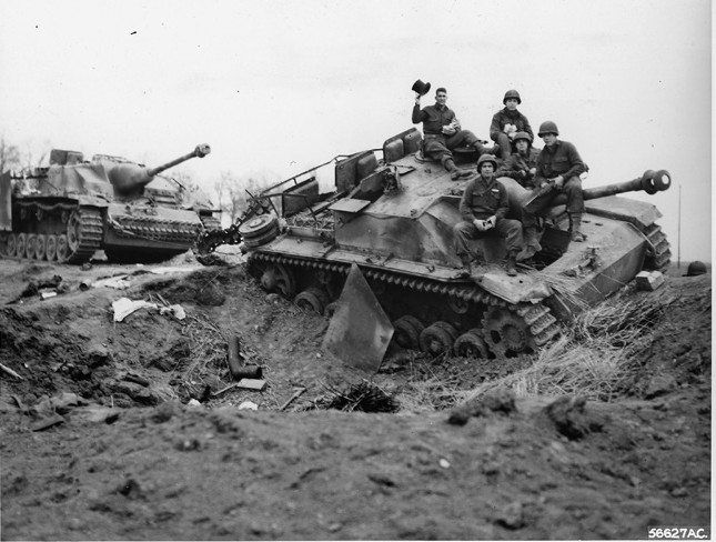 American soldiers near the town of Modrath, Germany, climb aboard and pose for a photo atop a German self-propelled assault gun that has fallen victim to fighter bombers of the Ninth Air Force.