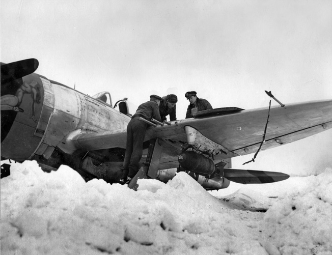 After their airfield has been cleared of snow to allow planes to take off, officers of the U.S. Ninth Air Force check the .50-caliber wing-mounted machine guns of a Republic P-47 Thunderbolt fighter bomber prior to a mission against enemy targets in Germany on February 6, 1945.
