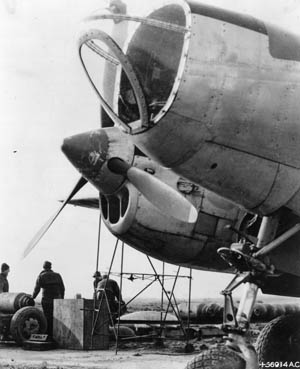 """Ground crewmen """"bomb up"""" and droop snoot a Lockheed P-38 Lightning fighter bomber in preparation for a raid on enemy installations in occupied France. This version of the famed Lightning is called a droop snoot because of its glass-enclosed nose and the addition of a bombardier during missions."""