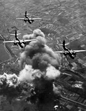 Smoke billows from the Aershot rail center 30 miles north of the Belgian capital of Brussels as three Douglas A-20 Hovoc light bombers from the Ninth Air Force speed away from the scene of destruction. The raid was conducted on May 7, 1944, a month before the D-Day landings in Normandy.