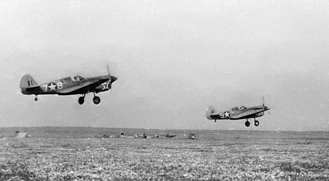 A pair of Curtiss P-40 Warhawk fighters takes off from an airfield in Egypt to strafe Axis troop and supply columns in the North African desert. These aircraft are part of the U.S. Middle East Air Force, and the photo was taken in July 1942.