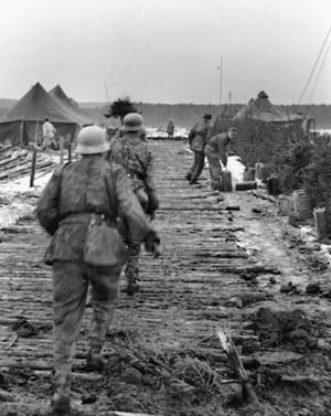 German soldiers hurriedly go through equipment and war matériel left behind by American troops who have recently abandoned their camp. Hitler's plan for the Ardennes Offensive included the use of captured American fuel; however, precious little American gasoline was found.