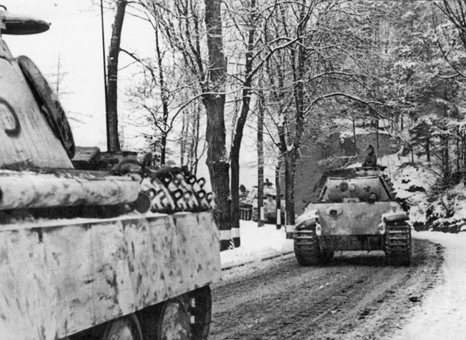 German Panther tanks roll along an unpaved road that has been hardened by freezing winter temperatures during the Battle of the Bulge.