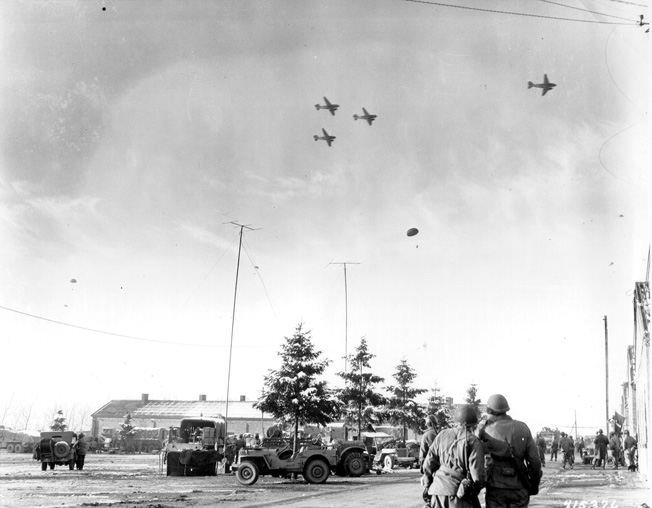 On the day after Christmas, 1944, Douglas C-47 transport aircraft drop provisions to American troops occupying Bastogne.