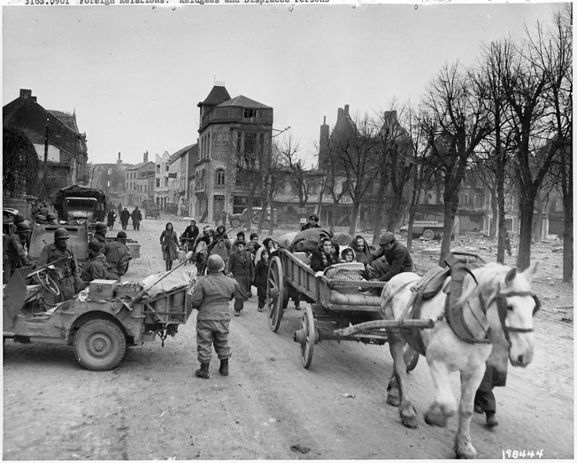 Much of the civilian population of Bastogne left the town with the approach of battle. Here, some of the townspeople, now refugees, seek safety. American troops have halted along the street, where no snow has fallen as of the date of this image.