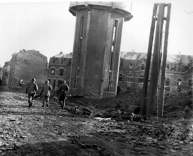 Their rifles slung over their shoulders, three men of the 101st Airborne Division walk down a rubble-strewn Bastogne street past the bodies of fellow soldiers killed by German bombing the previous night. This photograph was taken on Christmas Day, 1944, and the beleaguered defenders of the town were relieved the following day.