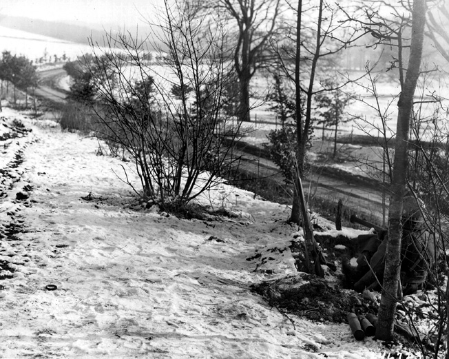 Manning a lonely outpost along a road leading into Bastogne, soldiers of the U.S. 101st Airborne Division point their bazooka in the direction of an expected German attack.