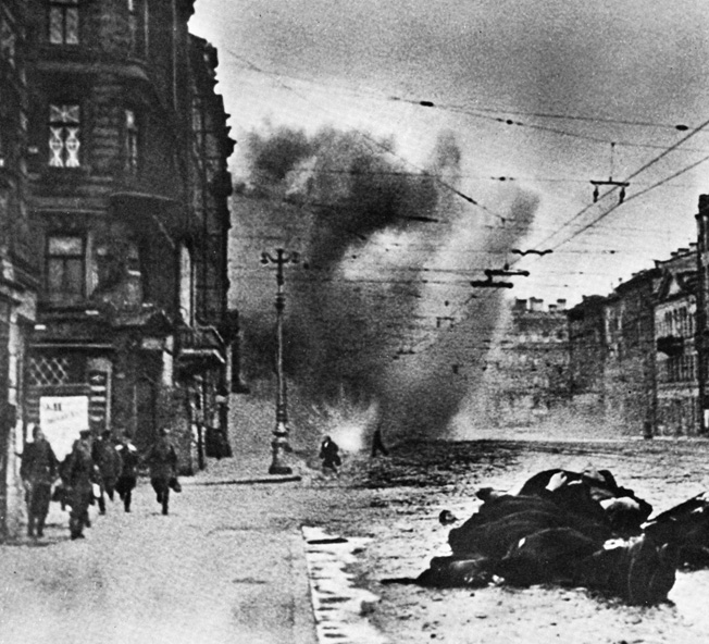 Soviet soldiers and civilians run for their lives along the Nevsky Prospekt, Leningrad's main boulevard, as German shells slam into the street and surrounding buildings. Bodies lie heaped together and unburied amid the destruction of war.