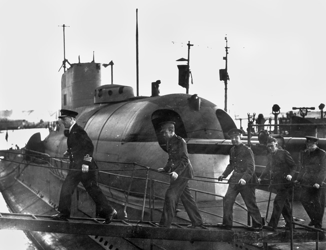 In company with a British naval officer, crewmen of the Surcouf leave the submarine. Tragically, violence broke out aboard the submarine as some officers opposed its being transferred to British control.