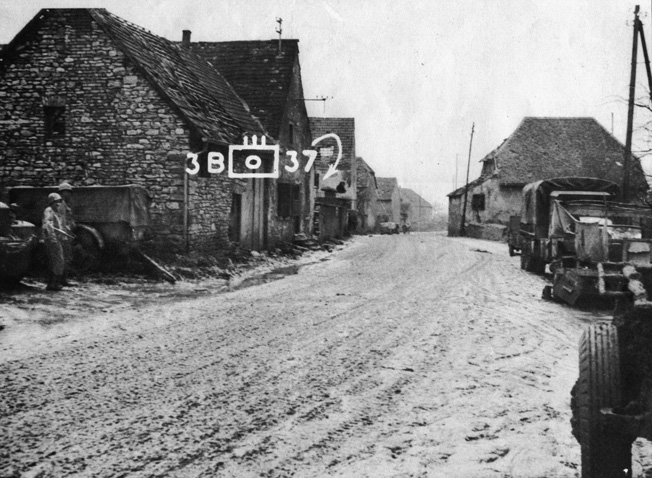 In this photo taken less than a week after the bitter fighting in Singling, positions occupied by American and German forces are seen looking to the northwest down the town's main street. German self-propelled guns were located at the far end of the street in order to command the whole length of the roadway. American tanks were positioned in the walled garden just behind the first house on the left.