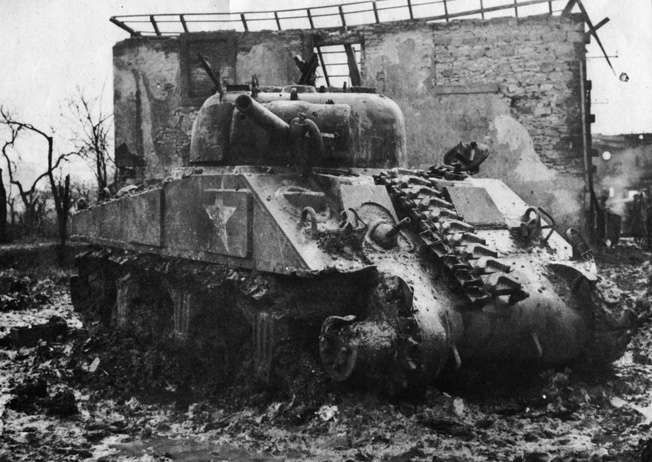 This Sherman tank commanded by Sergeant Giles W. Hayward was hit twice by German shells during the fight at Signling. The second shell struck the Sherman in its right sprocket, blowing off the tread and crippling the tank.