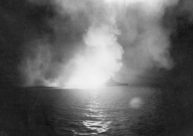 The victim of multiple Japanese torpedo hits at Pearl Harbor, the battleship USS West Virginia was raised from the bottom of the harbor and repaired to fight again. In this photo, West Virginia is illuminated as her guns take a toll on the Japanese during the Battle of Surigao Strait three years after Pearl Harbor.