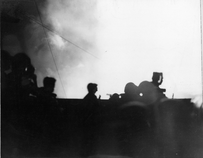The battleship USS Pennsylvania is silhouetted against the darkened sky by the gun flashes of her cohorts on the American battle line at Surigao Strait.