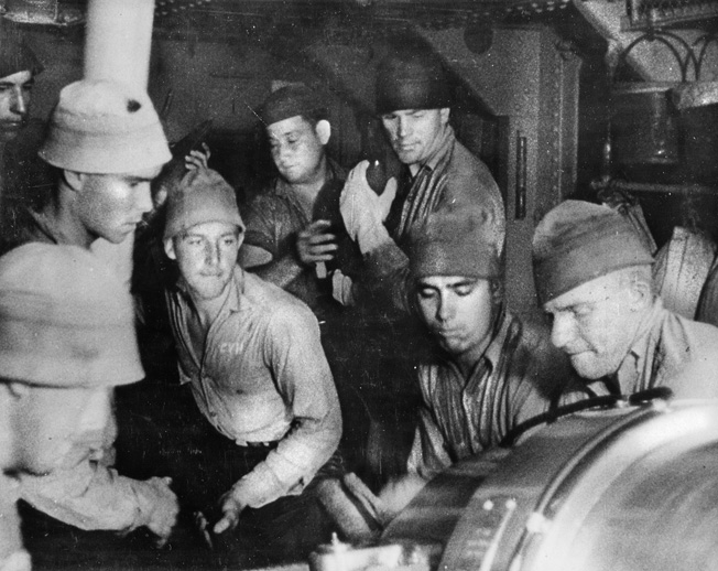 A casemate gun crew services its 5-inch weapon while a line of sailors passes ammunition forward. The 5-inch gun was the main armament of many American destroyers during World War II.
