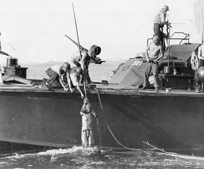 A U.S. PT Boat picks up Japanese survivors, clinging to debris in the water in Surigao Strait. The Navy seaman were warned to carefully search each prisoner to be sure they had no weapons.