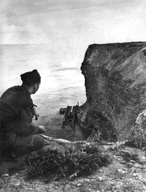 A Stars & Stripes reporter views a wrecked treadway  section of a Mulberry artificial harbor marooned below the cliffs of Pointe du Hoc, scene of U.S. Rangers' heroics.