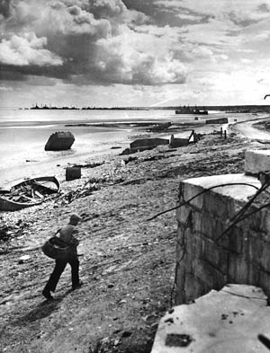 Frenchmen walks past a former German bunker on debris-strewn Omaha Beach near the Vierville exit where so much fierce fighting took place 12 months earlier.