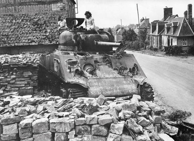 French children play atop a knocked-out Sherman tank that once belonged to the 3rd U.S. Armored Division.