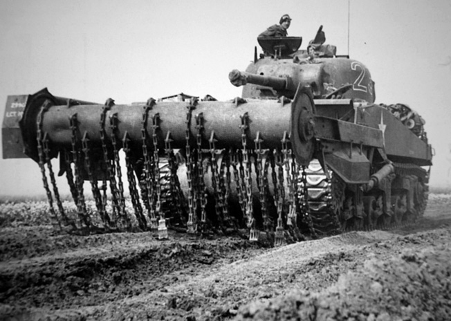 """An M4 Sherman """"Flail"""" or """"Crab"""" tank fitted with a rotating drum and chains that pounded the ground ahead of the vehicle to detonate land mines."""